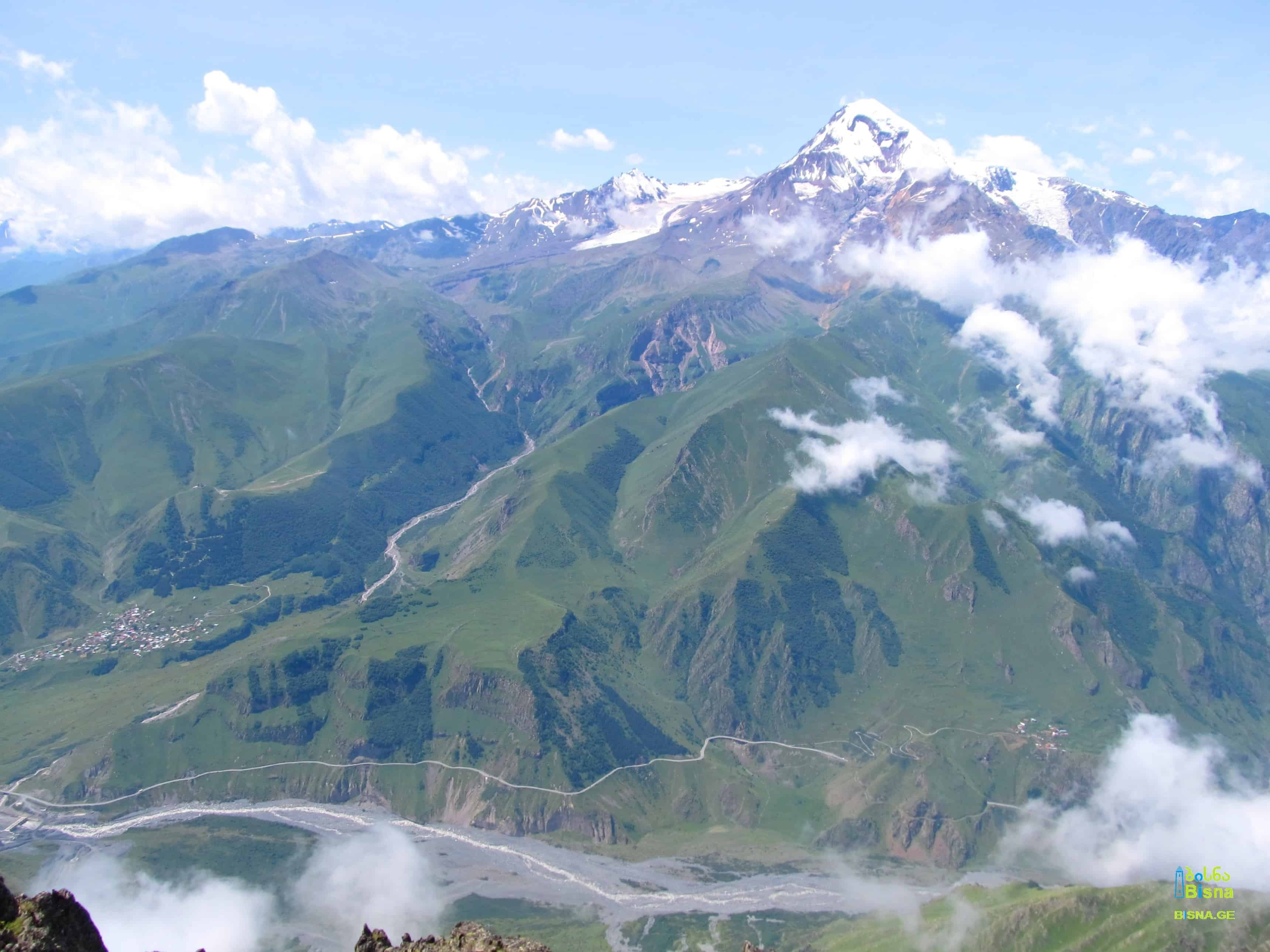 View on Mt. Kazbek, Holy Trinity Church of Gergeti and the begining of Dariali Valley from Khuro Range